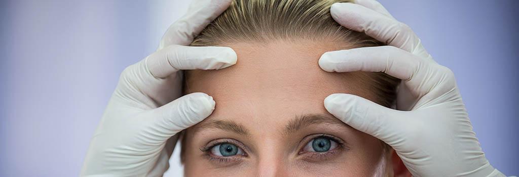 Na imagem aparece o rosto de uma mulher, com close na testa e na região dos olhos, e as mãos de um médico usando luvas cirúrgicas com os dedos polegares e indicadores posicionados na testa, simulando uma consulta.